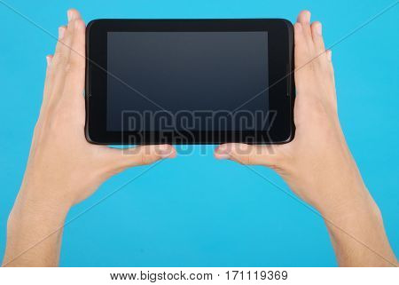 Male hand holding a touchscreen isolated on blue background
