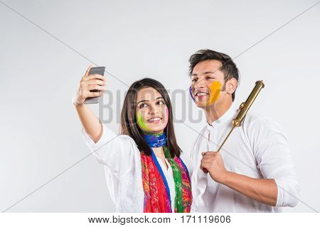 Festival and technology concept - indian young couple taking selfie or self picture using cel phone or smartphone on Holi festival