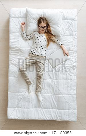 Almost like adult. Gorgeous determined pretty child sleeping soundly on white soft bed while imagining her future being businesswoman