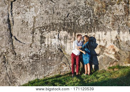 Nice couple standing near stone wall, outdoor. Beloved embracing and smiling. Woman wearing blue dress and light blue shoes and man wearing white shirt, black shoes and claret trousers. Full body. Copyspace