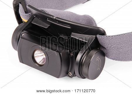 Black LED head lantern with elastic fixtures isolated on white background. Close-up