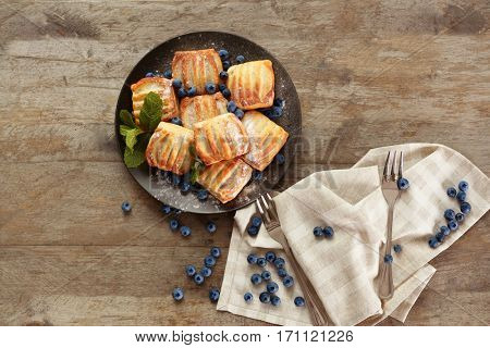 Sweet tasty pastries with bilberries on plate against wooden background, top view
