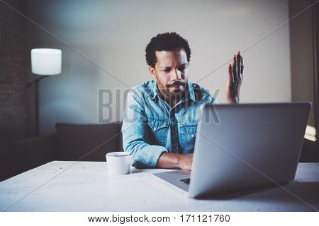 Indignant bearded African man making video conversation via laptop with partners while working at coworking office.Concept of young business people.Blurred background, film effect