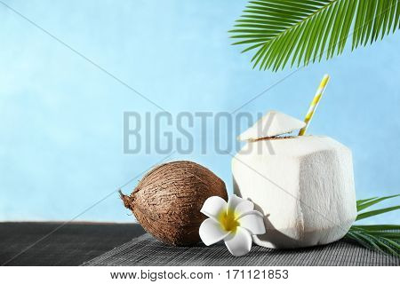 Coconut cocktail with plumeria and nut on color background