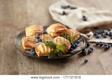 Sweet tasty pastries with bilberries on plate against wooden background