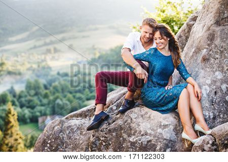 Nice couple sitting on high rock, outdoor. Girl leaning on her boyfriend's knee. Man holding her hand. Beloved looking down and smiling. Woman wearing blue dress and light blue shoes and man wearing white shirt, black shoes and claret trousers. Full body