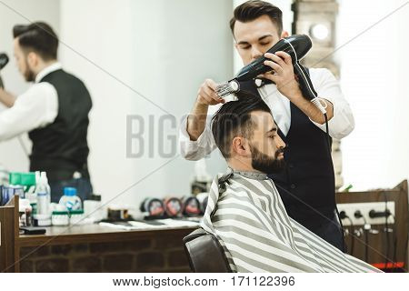 Handsome dark haired man wearing white shirt doing a haircut with hair dryer for man with black hair at barber shop, mirror at background, copy space.