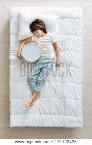 Better than Ringo. Cute committed charming child falling asleep in his bed after playing drum and still holding in in his hands poster