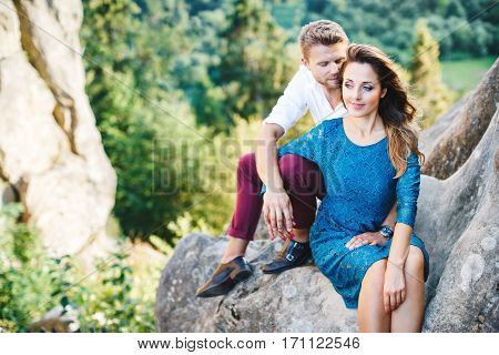 Nice couple sitting on high rock, outdoor. Girl leaning on her boyfriend's knee. Man holding his hand on girls knee. Man looking down and smiling and woman looking aside. Woman wearing blue dress and man wearing white shirt, black shoes and claret trouser