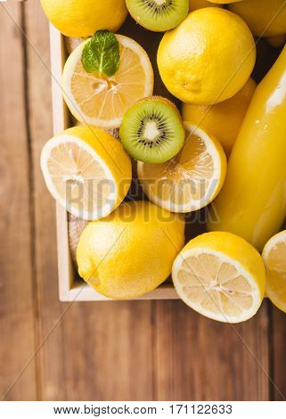 Orange juice detox juice lemon juice lemonade in a glass bottle in a box. Lemons in a wooden box on a wooden table. Lemons on a wooden background. Lemons. Fruits. Lemon halves. Mint. Healthy food concept. Copyspace