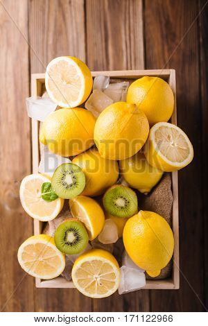Lemons and kiwi in a wooden box on a wooden table. Lemons on a wooden background. Lemons. Fruits. Lemon halves. Mint. Healthy food concept. Copyspace