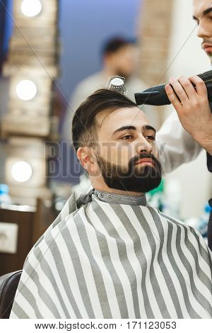 Man's hands doing a haircut with hair dryer and hair brush for man with black hair at barber shop, portrait, close up, copy space.