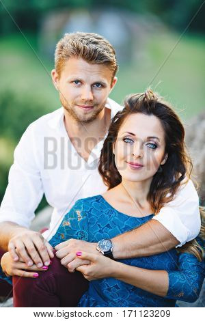 Nice couple sitting, outdoor. Girl leaning on her boyfriend's knee and holding his hands. Beloved looking at camera and smiling. Woman wearing blue dress and man wearing white shirt and claret trousers. Waist up, closeup