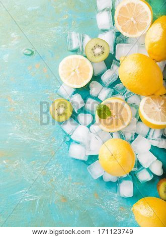 Lemons and ice on a turquoise background. Lemons. Fruits. Kiwi. Mint. Healthy food concept. Copyspace