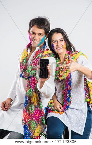 indian couple busy on smartphone on Holi festival, with face painted with colours, isolated over white background