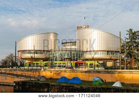 STRASBOURG FRANCE - FEB 2 2017: European Court of Human Rights in Strasbourg with tramway in tramway station and protesters camping tents