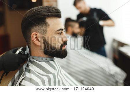 Portrait of man with beard, man wearing black shirt doing a haircut for man with long black hair at barber shop at background, copy space, close up.