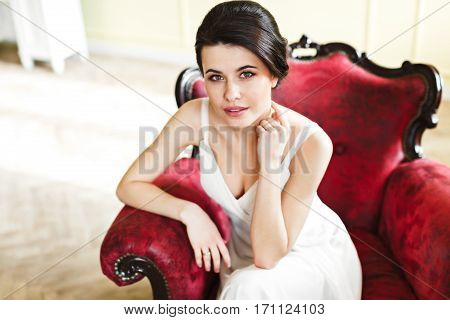Woman in white dress sitting on red armchair. Looking at camera. Kneeling on armchair, hand near face. Point of view. Indoor, interior, studio