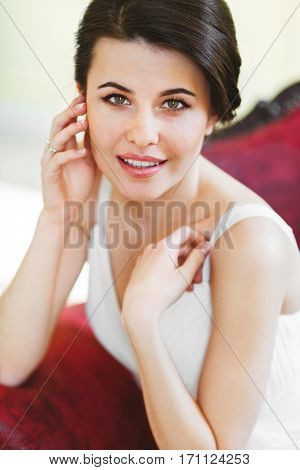Woman in white dress sitting on red armchair. Looking at camera and smiling. Kneeling on armchair, touching face and neck. Indoor, interior, studio