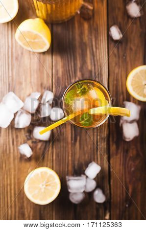 Lemon ice tea on brown wooden table with lemons around. Iced tea with lemon slices and mint on rustic background