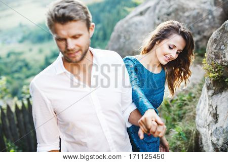 Nice couple on path among rocks. Man holding his girlfriend's hand and leading her. Girl looking down and smiling. Woman wearing blue dress and light blue shoes and man wearing white shirt, black shoes and claret trousers. Waist up