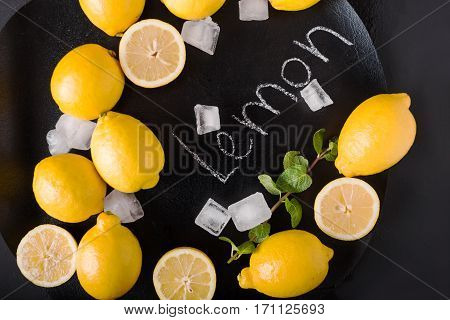 Word Lemon on chalkboard. Hand written. Copy space. Fitness and weight loss concept top view Blank board copy space. Lemons mint ice on a black background. Healthy food concept. Copyspace
