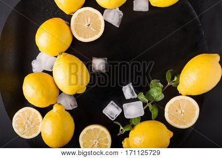Lemons mint ice on a black background. Healthy food concept. Copyspace