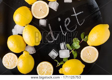 Word Diet on chalkboard. Hand written. Copy space. Fitness and weight loss concept top view Blank board copy space. Lemons mint ice on a black background. Healthy food concept. Copyspace