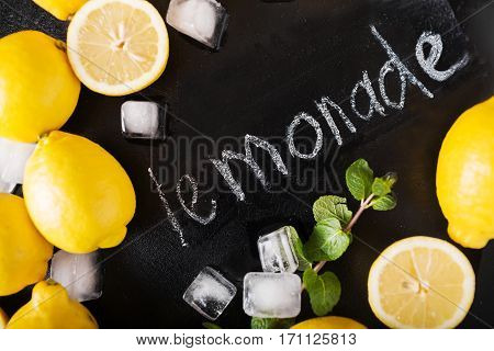 Word Lemonade on chalkboard. Hand written. Copy space. Fitness and weight loss concept top view Blank board copy space. Lemons mint ice on a black background. Healthy food concept. Copyspace