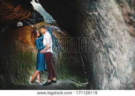 Nice couple in cave. Beloved embracing and looking at each other. Woman wearing blue dress and light blue shoes and man wearing white shirt, black shoes and claret trousers. Full body