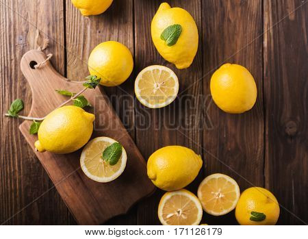 Half of lemon on a wooden board. Lemons on a wooden background. Lemons. Fruits. Lemon halves. Mint. Healthy food concept. Copyspace
