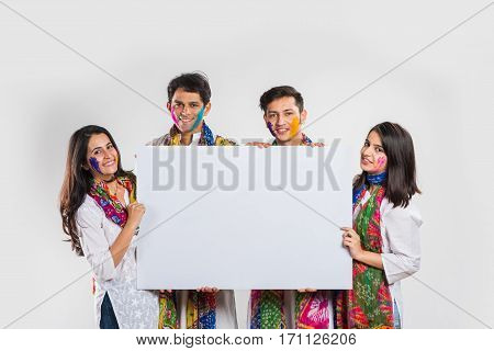 two young beautiful indian couples holding or presenting white board with copy space on the occasion of Holi festival with faces painted with Gulal colours, isolated over white background