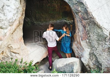 Couple getting out the cave. Man helping girl, holding her both hands, rear view. Woman wearing blue dress and man wearing white shirt, black shoes and claret trousers. Full body