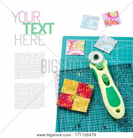 Stitched square pieces of fabric of quilt with rotary knife and ruler on craft mat on white surface