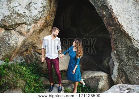 Couple near the cave. Man holding girl's hand. Beloved looking at each other. Woman wearing blue dress and light blue shoes and man wearing white shirt, black shoes and claret trousers. Full body