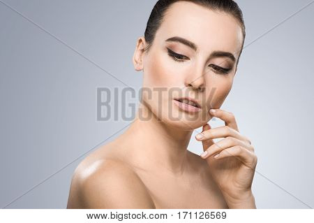 Model looking down. Head a little bit aside. Wearing pigtail, nice make-up. Thoughtful girl. Finger touching chin. Beauty portrait, head and shoulders. Indoor, studio