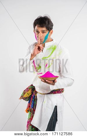 indian man standing with gulal colour in plate on holi festival in keep silence sign, isolated over white background