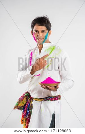 indian man standing with gulal colour in plate on holi festival pointing finger or presenting something on white background