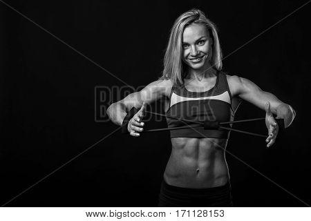 Beautiful female bodybuilder on a dark background.