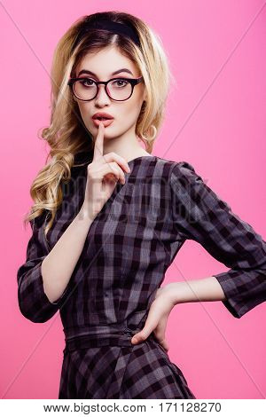 Pretty girl with light curly hair and pretty make up wearing in 60s style dress and glasses, holding hand on waist and showing shush, portrait, posing.