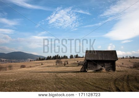 Old barn in the middle of an field.