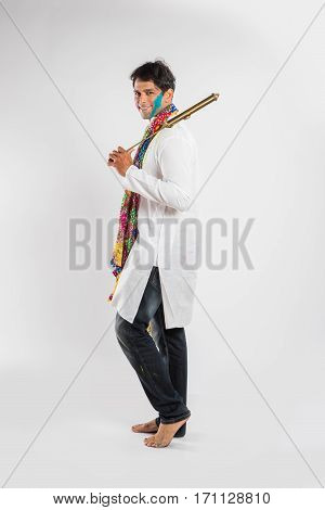 indian young man posing with pichkari on holi festival, isolated over white background