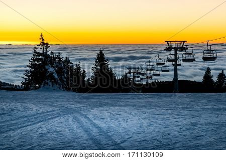 Chair ski lift with skiers silhouettes at sunset