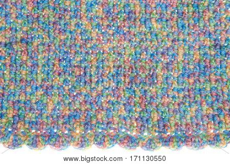 Baby blanket close up on crochet pattern alternating front loop double crochet with back loop double crochet scalloped pattern edge on base. Multicolored yarn green blue yellow purple orange.