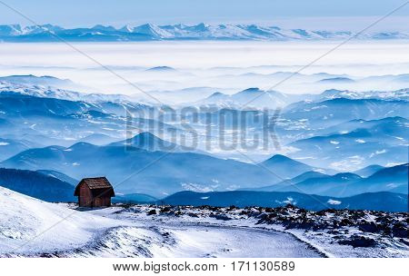 Mountain cabin with the view on mountain ranges under the snow, fog and clouds, mountain Kopaonik, Serbia