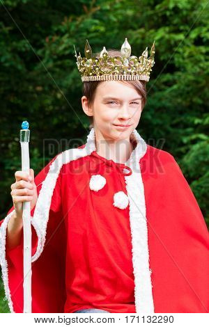 Cute teenager boy wearing crown and red costume holding a scepter pretending to be a king