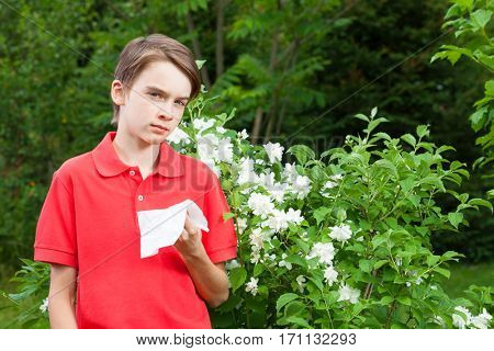Teenager boy with hay fever holding tissue allergic to bloom flowers in a spring garden