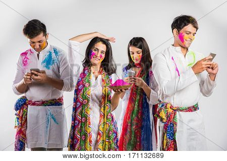 three young indians busy in social media on smartphones on the occasion of holi festival, one female with with colours in hand showing worried expressions, isolated over white background