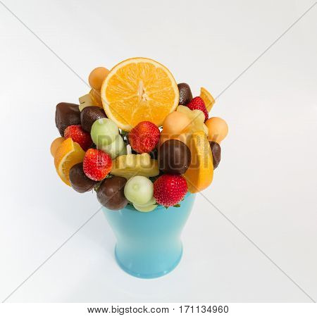 nice amazing closeup view of assorted natural appetizing, fresh fruits mixed with dark chocolate in ceramic blue vase on light grey background