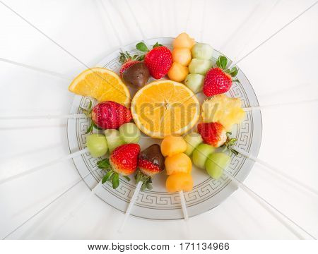 amazing gorgeous closeup view of various assorted appetizing fruits in ceramic plate on light grayish background